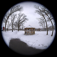 Wantagh, New York, USA. February 20, 2019. Snow falls at Mill Pond Park, with partly shoveled path leading to wood gazebo and bare trees, on Long Island. 180 degree fisheye view of Nassau County public park.