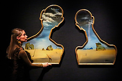 © Licensed to London News Pictures. 29/01/2020. London, UK. A staff member holds Salvador Dalí, Couple aux têtes de pleins nuages (1937) (est £7m to £10m) at the preview of Bonhams Impressionist and Modern Art Sale. Photo credit: Dinendra Haria/LNP