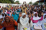 Ladies attending the first-ever international Conference on Womens' Challenge in Darfur, raise their hands in the hope of peace while gathering to hear speeches by the British peer Lord Ahmed and traditional songs by local singers just outside the compound walls belonging to the Govenor of North Darfur in Al Fasher (also spelled, Al-Fashir) where the women from remote parts of Sudan gathered to discuss peace and political issues and celebrate Darfurian culture.