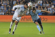 Forward Giles Barnes #28 of the Vancouver Whitecaps FC heads a shot on goal against mid-fielder Graham Zusi #8 of Sporting Kansas City during the first half at Children's Mercy Park in Kansas City, Kansas.