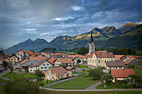 Scenic photo of a small town nestled in the countryside outside of Gruyere, Switzerland