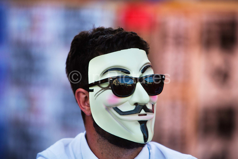 """Glastonbury Festival, 2015. Shangri La is a festival of contemporary performing arts held each year within Glastonbury Festival. The theme for the 2015 Shangri La was Protest. <br /> Man appearing in public as Anonymous, wearing Guy Fawkes mask with sunglasses over it.<br /> Anonymous is a loosely associated international network of activist and hacktivist entities. A website nominally associated with the group describes it as """"an internet gathering"""" with """"a very loose and decentralized command structure that operates on ideas rather than directives"""". The group became known for a series of well-publicized publicity stunts and distributed denial-of-service (DDoS) attacks on government, religious, and corporate websites."""