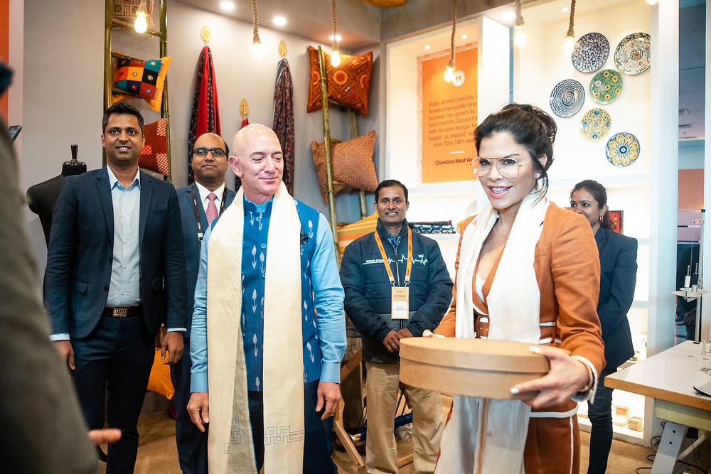 NEW DELHI, INDIA – JANUARY 15, 2020: Amazon president Jeff Bezos and Lauren Sanchez receive a gift from a handicraft artisan booth at the 2020 Microsoft SMB Summit at Jawaharlal Nehru Stadium.