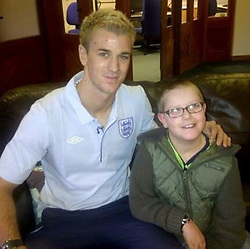 © Licensed to London News Pictures . 12/08/2017 . Manchester , UK . COLLECT PHOTO of Connor Shaw (r) pictured with footballer Joe Hart (l) , who has supported him as he has grown up . Connor Shaw SHAW (17 - turns 18 today - 13/08/2017) in his home ahead of his birthday . The Banksy stencil on the wall has significance as his parents say it represents the girl who died and whose heart Connor received in a life-saving heart transplant operation . When he was born doctors said he wouldn't live long due to a heart condition but he's doing well after receiving expert care , multiple operations and a heart transplant . His parents are campaigning for an opt-out organ donor register . See http://www.manchestereveningnews.co.uk/news/greater-manchester-news/never-thought-son-would-reach-13469965 for more information