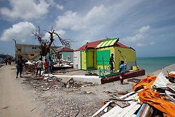 Residents stand around destroyed houses during France's President Emmanuel Macron's visit in the French Caribbean islands of St. Martin, Tuesday, Sept. 12, 2017. Macron is in the French-Dutch island of St. Martin, where 10 people were killed on the French side and four on the Dutch. Photo by Christophe Ena/Pool/ABACAPRESS.COM