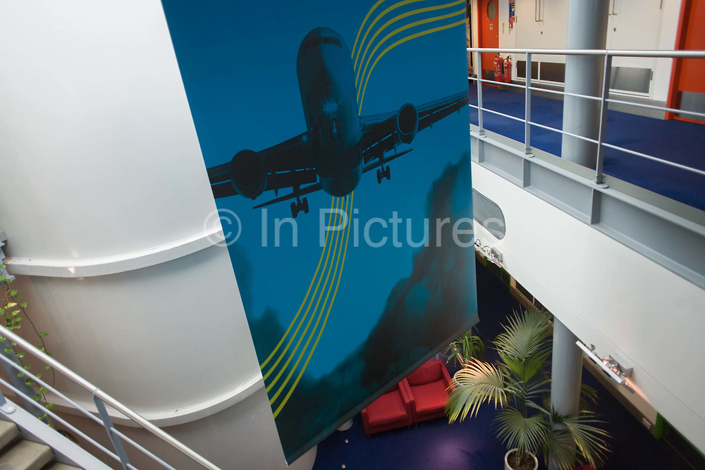 Heathrow airport's NATS Air Traffic Control tower, London, England. On the ground floor we see a NATS illustration of a flying airliner on the tower's lift shaft. Controlling aviation traffic on the ground and in the controlled airspace around London, the NATS controllers help safely guide up to 6,000 flights a day from the top of the 87 metre high tower, handling 1,350 aircraft movements a day into Heathrow.