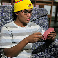 Asia, Nepal, Kathmandu. Teenager playing cards.