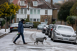 © Licensed to London News Pictures. 08/02/2021. Surrey, UK. A member of the public walks past snow covered cars and streets in Putney, South West London this morning as Storm Darcy is forecast to bring more snow and freezing temperatures today. The Met Office have issue numerous weather warnings today for more snow and ice with disruption to travel, power cuts and possible stranded vehicles over the next five days with highs of only 0c.  Photo credit: Alex Lentati/LNP