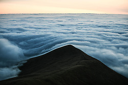 © Licensed to London News Pictures. 08/08/2020. City, UK. A blanket of cloud covers the landscape as seen from the summit of Pen-y-Fan in the Brecon Beacons, on what is expected to be the hottest day of the year across the UK. The mountain which is the highest in southern Britain, has become increasingly popular with visitors who reach the top of the peak at first light to see the sun rising from the horizon. Photo credit: Robert Melen/LNP