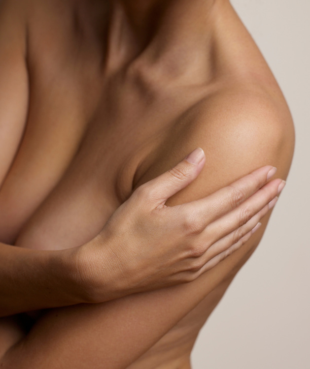 Woman caressing her beautiful and graceful nude torso and arm