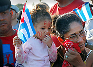 """A young child wears """"Yo Soy Fidel"""" painted on her face as Cubans react to seeing the funeral procession carrying the ashes of Fidel Castro on the road to Cemeterio Santa Ifigenia in Santiago de Cuba on Sunday, December 4, 2016."""