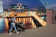 A father pushes his child's buggy past a CCTV and a onstruction hoarding, a night time panorama of the Thames south bank, featuring the HQ of the intelligence service (MI6) across the river in Vauxhall.