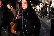 Woman listening to music on her white iPhone headphones. London, UK. Reminiscent of the original iPod advertising campaign.