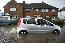 © London News Pictures. 12/02/2014. Egham, UK.  Residents of Egham in Surrey try to move a car caught in flood water. Torrential rain in the area is due to raise water levels increasing the risk of further flooding. Photo credit : Ben Cawthra/LNP