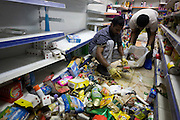 Cleaning up the remnants of the Clarence Road Convenience Store. After the riots of London and other UK cities, Sri Lankan-born Sivaharan (Siva) Kandiah's looted shop 'Clarence Convenience Store' in Clarence Road, Hackney.