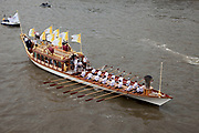 London, UK. Friday 27th July 2012. The London 2012 Olympic Games torch makes it's way up the River Thames on the final day of the torch relay. The pageant, led by the official royal barge, Gloriana was flanked by a flotilla of other rowing boats and vessels.