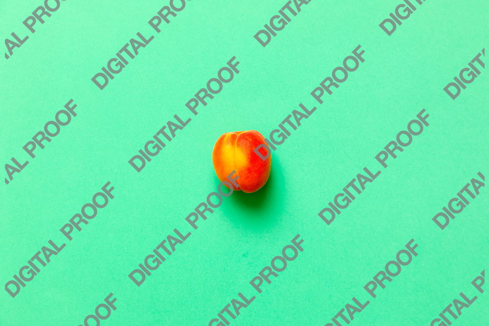 Lonely Apricot  isolated over a green background viewed from above, flatlay style