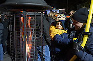 Goshen, New York - Mike Pagliocca holds his son Jackson, 4, as they try to keep warm at a heater during the Illuminate Goshen New Year's Eve Ball Drop on Dec. 31, 2016.