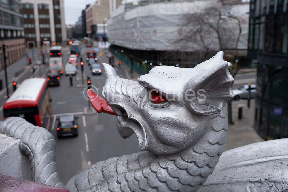 A City of London dragon boundary mark at Holborn Viaduct on 5th March 2021 in London, United Kingdom. The dragon boundary marks are cast iron statues of dragons on metal or stone plinths that mark the boundaries of the City of London painted silver, with details of the dragon wings and tongue picked out in red.