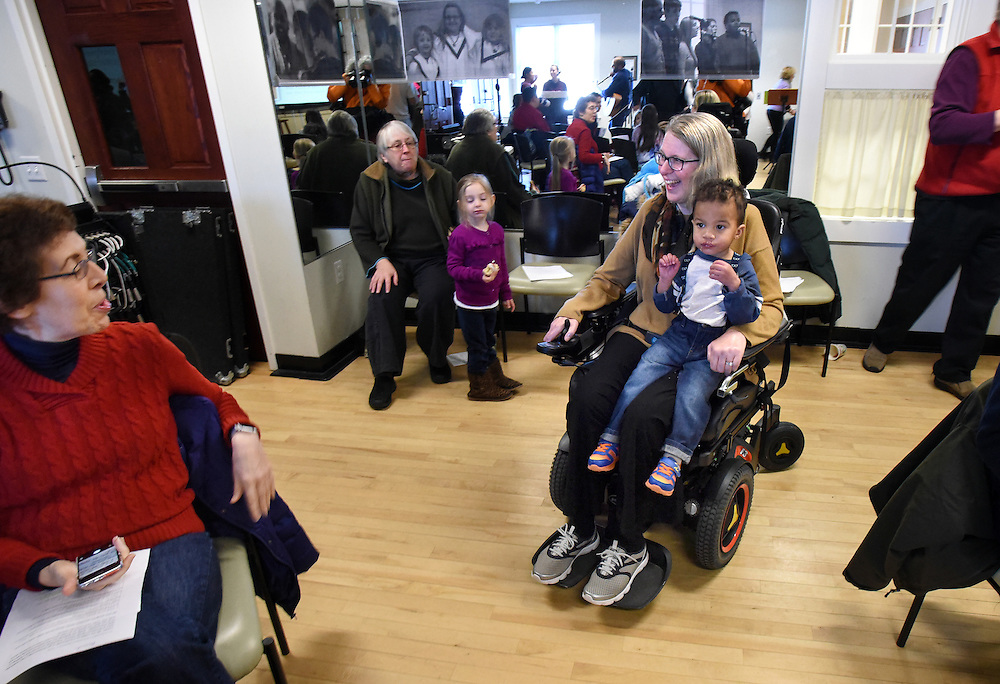 Mara Lavitt -- Special to the Hartford Courant<br /> February 14, 2016, Glastonbury<br /> Amyotrophic Lateral Sclerosis (ALS) forced Nancy Butler of Marlborough to step down as pastor of the Riverfront Family Church in Glastonbury during the Sunday service. Butler with one of her grandchildren Theeran Arulampalam age 2 of Hartford wheels in for the start of the service. Amanda Fecteau of Manchester is at left.