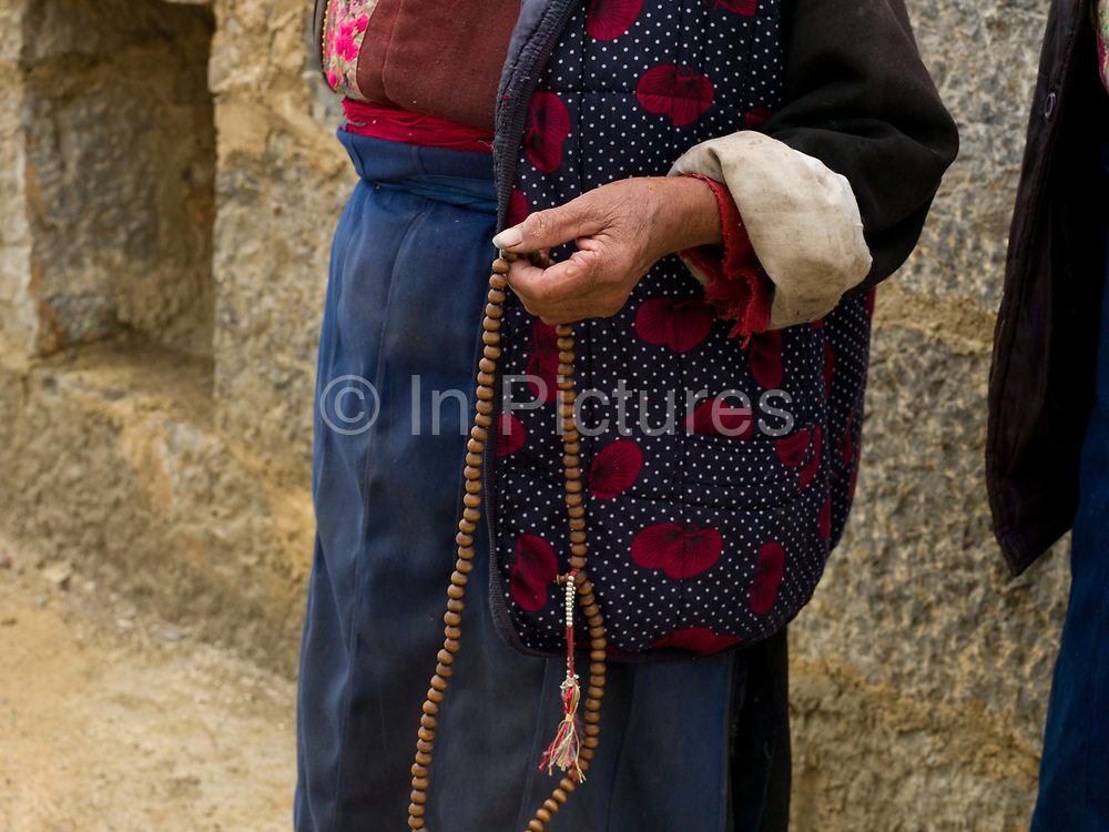 An elderly Tibetan woman performing her prayers (which she does several times a day) whilst circulating the stupa (chorten in Tibetan), Tangu, Yunnan province, China. Stupas are important religious monuments for Tibetans. This unique religious architectural form expresses significant religious symbolism and presents Buddha's physical presence. It generally consists of three parts; a whitewashed base, a whitewashed cylinder and a crowning steeple or shaft.