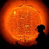 Silhouette of steel worker in front of glowing hot orange