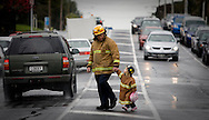 Two and a half year-old Imogen arrives hand in hand with her dad John Boyd at a Fireman's protest over contract negotiations at the opening of a new Fire Station in Mt Roskill, Auckland, New Zealand. September 2009. <br /> Photograph Richard Robinson.<br /> 2009 © New Zealand Herald A Division of APN New Zealand Ltd.<br /> No Reproduction without prior written permission. Contact www.newspix.co.nz to licence photograph.