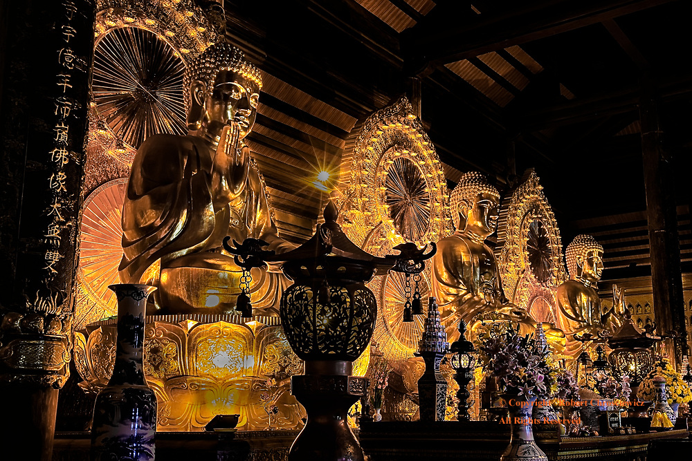 The main alter in the Bái Đính Temple displays three prominent Buddhas along with numerous other smaller statues, flowers and other offerings, Ninh Binh Vietnam.