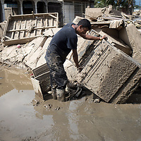 A man recovers a cooking stove from the mud in La Planeta, San Pedro Sula, Honduras, after hurricane Eta.<br /> <br /> Hurricanes Eta and Iota hit hard on the north coast of Honduras, leaving some areas flooded for three weeks, destroying people's furniture, belongings, vehicles and houses as well as standing crops.