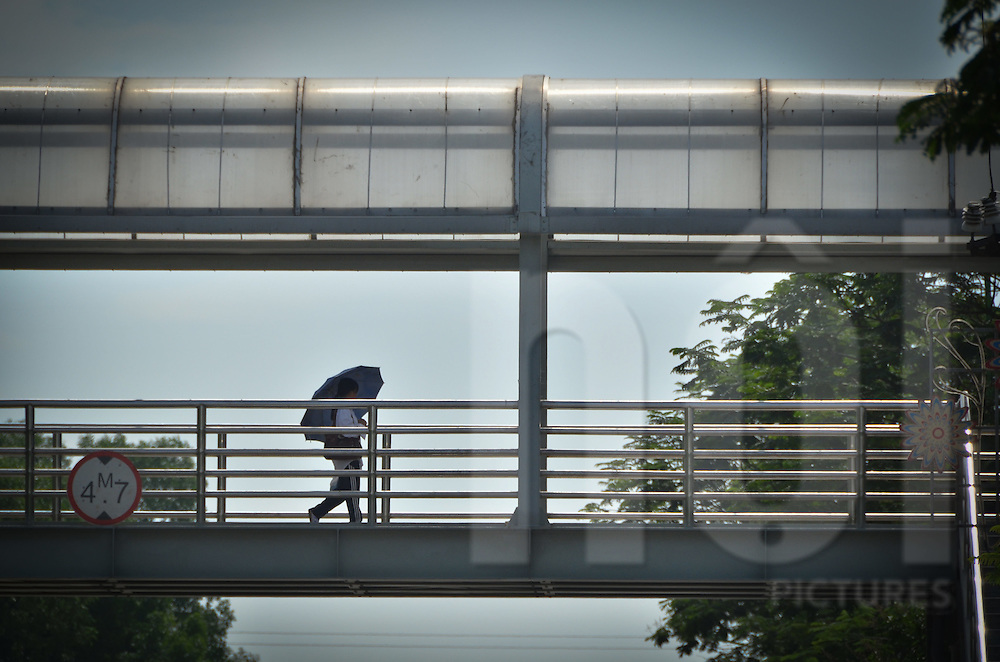 A girl carries an umbrella to protect herself over the sun is walking on a footbridge in Hoang Quoc Viet, Cau Giay district, Hanoi, Vietnam, Asia