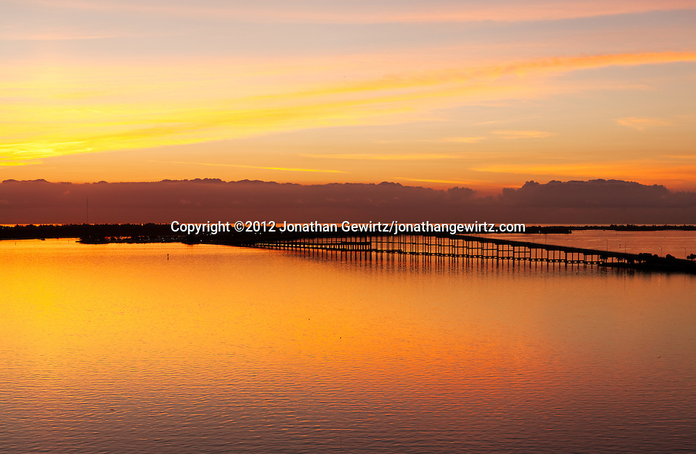 The rising sun casts a beautiful orange light on the William Powell Bridge, Rickenbacker Causeway and Virginia Key, just offshore from Miami, Florida. WATERMARKS WILL NOT APPEAR ON PRINTS OR LICENSED IMAGES.
