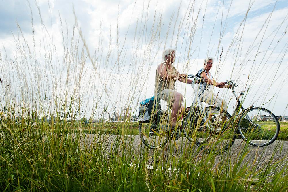 Nederland, Lent, 4 juli 2012.Twee oudere vrouwen fietsen over de dijk langs de Waal bij Lent..Foto (c): Michiel Wijnbergh