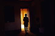 """An orphan of Burundi's ethnic conflict, stands in the door of her house built by Marguerite Barankitse (known as the 'Angel of Burundi') in 1994. During the genocide, Barankitse, at great personal risk, managed to save 25 orphans, Hutu, Tutsi and Twa and built a home for them. Currently, she has helped more than 10,000 orphans and separated children who can grow up in an """"extended adopted family"""" in security, education and love. Burundi now has many 'child headed households'"""