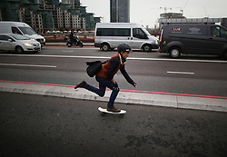 © Licensed to London News Pictures. 19/11/2015. London, UK.   A commuter uses a skateboard on the newly opened Cycle Superhighway 5 on Vauxhall Bridge. Dedicated cycle lanes are being installed throughout the capital.  Photo credit: Peter Macdiarmid/LNP