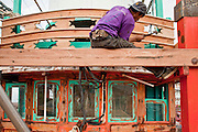 Sept. 24, 2009 -- PATTANI, THAILAND: A worker does wood finishing work on a fishing boat being rebuilt in Siriudom Shipyards in Pattani, Thailand. Fishing is the main industry in Pattani, one of just three Thai provinces with a Muslim majority. Thousands of people, mostly Buddhist Thais and Burmese Buddhist immigrants, are employed in the fishing industry, either crewing ships, working in processing plants or working in the ship building and refreshing yards.   Photo By Jack Kurtz / ZUMA Press