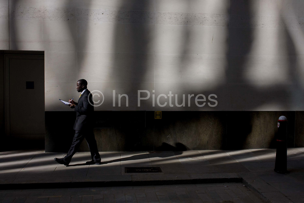 A black gentleman walks along a sunlit corner of a City of London lane. Carrying a clipboard he makes notes on a problem while walking beneath surreal patterns reflected by surrounding office buildings nearby, on to the wall above.