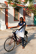 A schoolgirl on her bicycle after school, Pondicherry, India. Pondicherry now Puducherry is a Union Territory of India and was a French territory until 1954 legally on 16 August 1962. The French Quarter of the town retains a strong French influence in terms of architecture and culture.