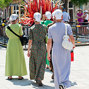 A group of modestly dressed women (Mennonites) wearing a short veil walk in the sun on the day the Italian Government and Heath Ministry has issued several warning for the current heath wave