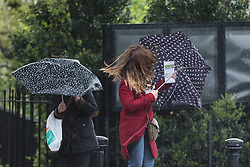 © Licensed to London News Pictures. 30/04/2018. London, UK. A tourist struggles to read her map during wet and windy weather at the top of the hill in Greenwich Park in London. The capital has been experiencing heavy rain and windy weather today. Photo credit: Vickie Flores/LNP