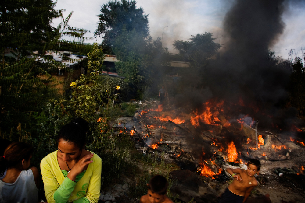 Crowds arrive from around Nova Gazela to witness a house fire on the day before relocation. The suspected arson happened in an abandoned home in a remote part of the camp.