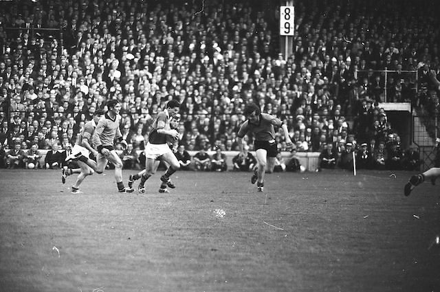 Kerry player in possession runs with the ball as Down player attempts to block him during the All Ireland Senior Gaelic Football Final Kerry v Down in Croke Park on the 22nd September 1968. Down 2-12 Kerry 1-13.