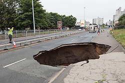 © Licensed to London News Pictures . 14/08/2015 . Manchester , UK . A large hole which has opened up beneath the A57 Mancunian Way motorway through Manchester City Centre , forcing the closure of the road . Heavy rain and flooding rushing through a culvert beneath is believed to have lead to the road collapsing . Photo credit : Joel Goodman/LNP