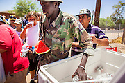 """20 JUNE 2012, PHOENIX, AZ:  Street people reach into a cooler for cold water and fruit juice in Phoenix, AZ, Wednesday. June 20 is the first day of summer in the northern hemisphere. The high temperature in Phoenix Wednesday soared to over 110 (F), well above the normal of 105. The hot weather is especially stressful on the homeless, who don't have the opportunity to get into air conditioning or access to cold water. """"I Will Listen,"""" an outreach organization that assists the homeless and community of street people in Phoenix, AZ, provides free food and cold drinks to the homeless in central Phoenix. They ran out of drinks and food in about one hour during Wednesday's outreach.        PHOTO BY JACK KURTZ"""