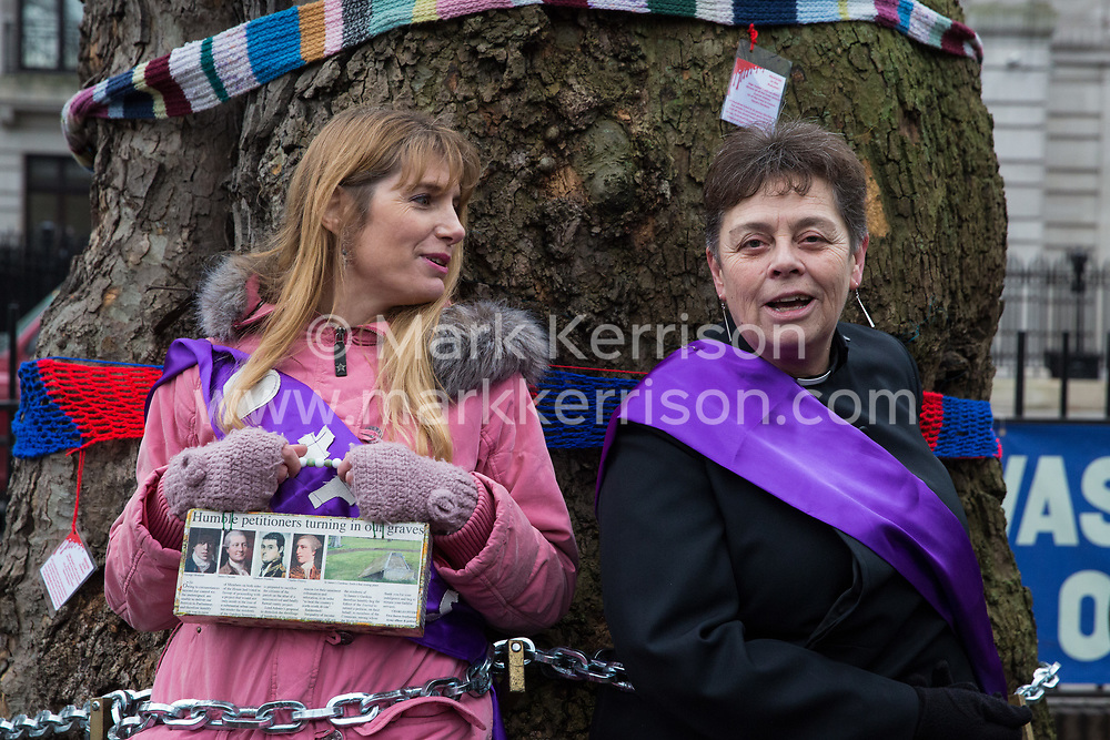 London, UK. 12th January, 2018. Anne Stevens (r), the vicar of St Pancras church, stands chained with local resident Jo Hurford (l) to a tree outside Euston station during a protest against the HS2 high-speed rail link. The protest formed part of a campaign by local residents against the planned felling of mature London Plane, Red Oak, Common Whitebeam, Common Lime and Wild Service trees in Euston Square Gardens to make way for temporary HS2 sites for construction vehicles and a displaced taxi rank.