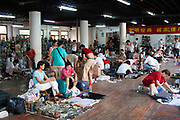 Stall owners in the indoor antique market in Yu Yuan Garden, downtown Shanghai, China. The pots and ceramics being sold by this family business on the top floor of the market are not genuine antiques. Many are fakes, which are sold to the more gullible tourists. Genuine antiques can be bought but the prices reflect their age considerably.