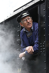 © Licensed to London News Pictures. 13/05/2016. Haworth, UK. The driver of a War Department 2-8-0 engine hangs out of the window whilst in Haworth train station on the Keithley and Worth Valley Railway Line. Today is the first day of the annual 1940's weekend in Haworth, West Yorkshire.  Photo credit : Ian Hinchliffe/LNP