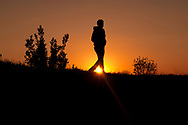 Silhouette of a man walking in a meadow during sunset