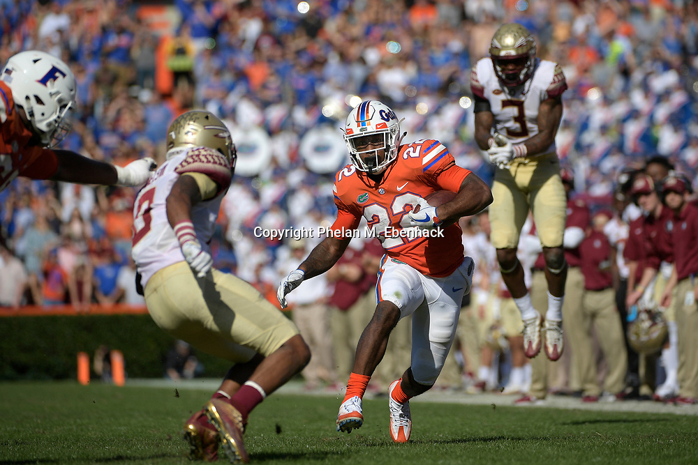 Florida running back Lamical Perine (22) runs after catching a pass between Florida State defensive back Derwin James (3) and defensive back Stanford Samuels III (8), left, during the first half of an NCAA college football game Saturday, Nov. 25, 2017, in Gainesville, Fla. (Photo by Phelan M. Ebenhack)