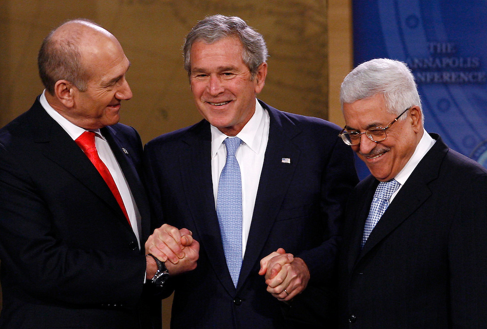 Israel's Prime Minister Ehud Olmert, U.S. President George W. Bush (C) and Palestinian President Mahmoud Abbas (R) hold hands on the podium at the Israel-Palestinian Peace Conference at the U.S. Naval Academy in Annapolis, November 27, 2007. Reuters/Jim Young