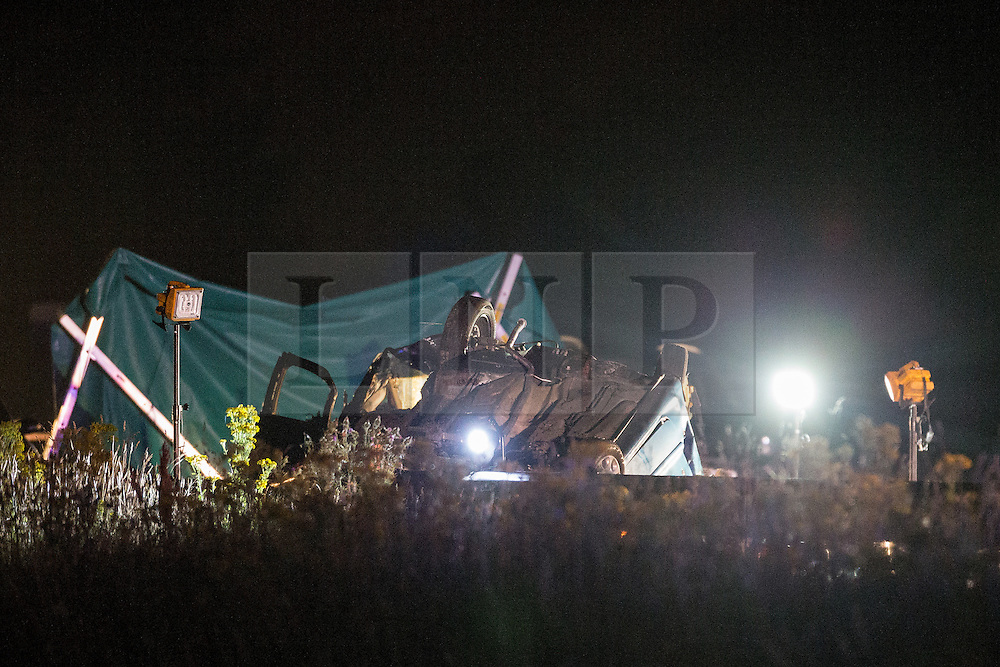 © Licensed to London News Pictures . 21/07/2014 . Nottinghamshire , UK . An overturned car with a tarpaulin erected behind . Police , fire crew and ambulances on the A1 road in Ranby yesterday morning (21st July 2014) following a fatal multi vehicle accident . Leroy and Sheila Carrington (aged 68 and 58) died at the scene when the Peugot 206 they were driving collided with a Vauxhall Astra . Roderick Franks (58) , who was a passenger in the Astra , died in hospital , following the crash . The road was closed in both directions whilst police investigated the scene .  Photo credit : Joel Goodman/LNP